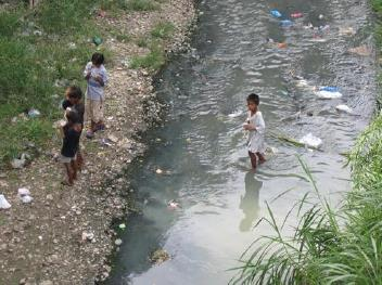 Image of children playing in river which filthy water flows through