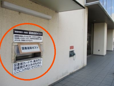The building front of Tozuka center faces Tozuka library book return box and is on the left.