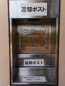 La Naka Biblioteca libro retorno caja está en el lado correcto de la entrada delantera.