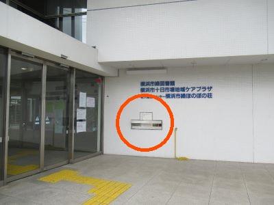 Una puerta del edificio va a la Midori Biblioteca libro retorno caja y está en el derecho.