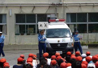 Ésta es la imagen que un guardia del cruce parece explicar a un (niños) escolares (gakudo) primario en una verdadera aula de seguridad de tráfico de niño.