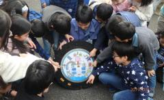 Photograph of children touching at design manhole