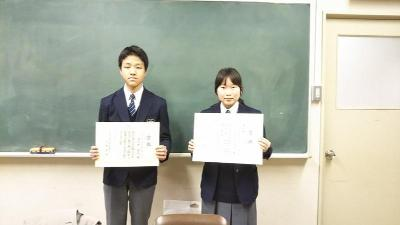 Yuta Tsukui of prize winner standing with certificate of merit, Igarashi moon Nagisa